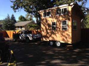 Image: Tiny house being drawn into position by small truck.