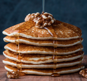 A stack of pancakes with syrup pouring from above.